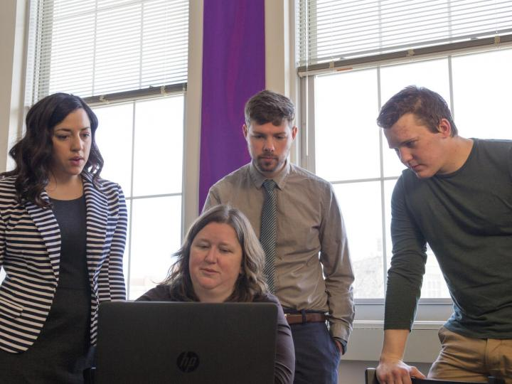 professor and students viewing computer screen